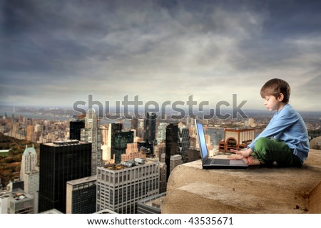 child with laptop on the top of NY city