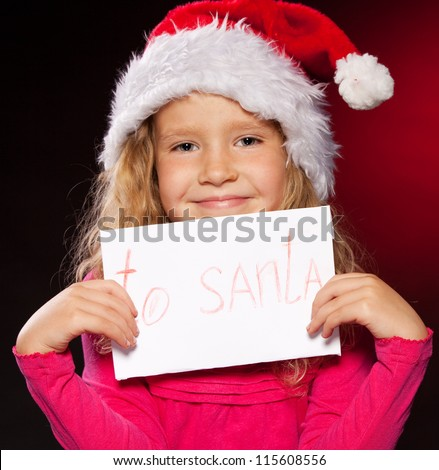 Child with letter to Santa Claus. Little girl in christmas hat on black background