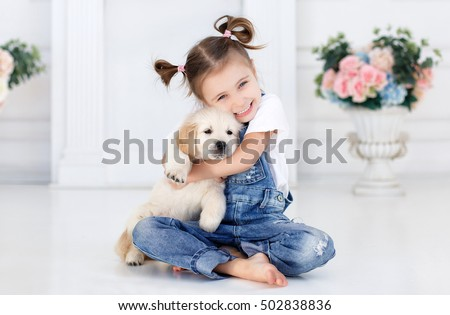 child with little dogs playing at home. girl with puppies. chid with puppy. kissing, hugging, playing in room