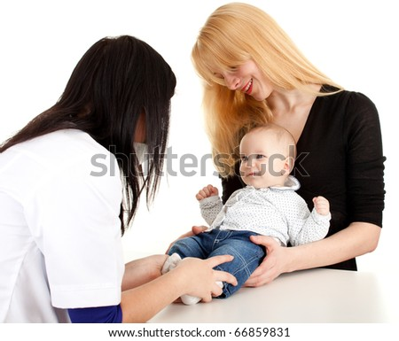 child with mother at doctor - female doctor examining baby