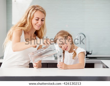 Child with mother drinking water from glass. Happy family at home in kitchen  #426130213
