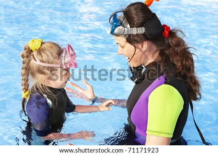 Child with mother in swimming pool learning snorkeling.