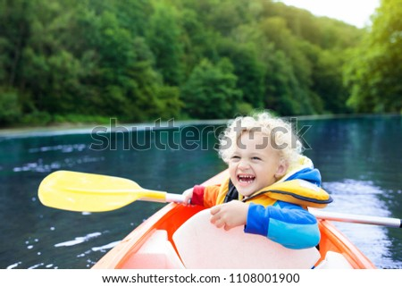 Child with paddle on kayak. Summer camp for kids. Kayaking and canoeing with family. Children on canoe. Little boy on kayak ride. Wild nature and water fun on summer vacation. Camping and fishing.