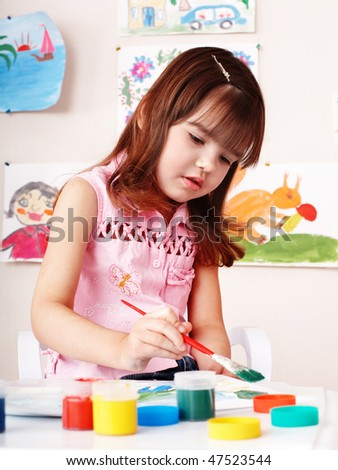 Child with picture and brush in play room. Preschool.