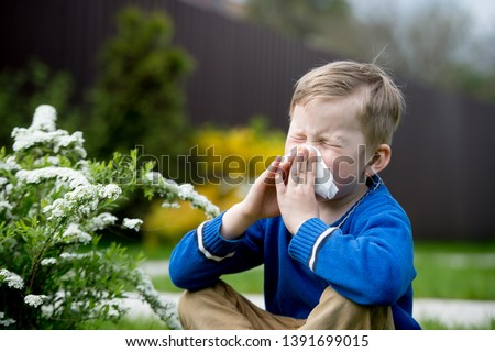 Child with pollen allergy. Boy sneezing and blowing nose because of seasonal allergy while sitting in a grass. Spring allergy concept. Flowering bushes and trees in background. Child allergy Stock photo ©
