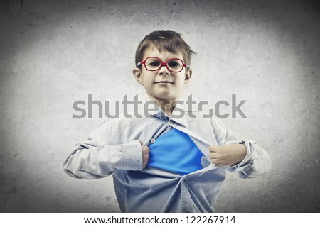 Child with red glasses opening his shirt like a superhero