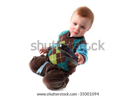 child with remote control isolated on white. toddler with technology in hand and expression of concentration