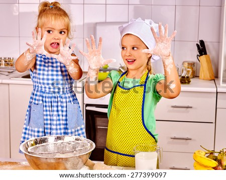 Child with rolling-pin dough at kitchen. Messy kids