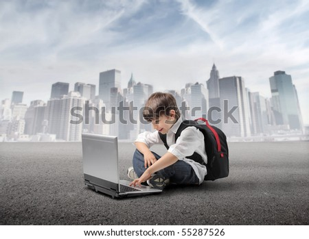 Child with rucksack sitting in front of a laptop with cityscape on the background