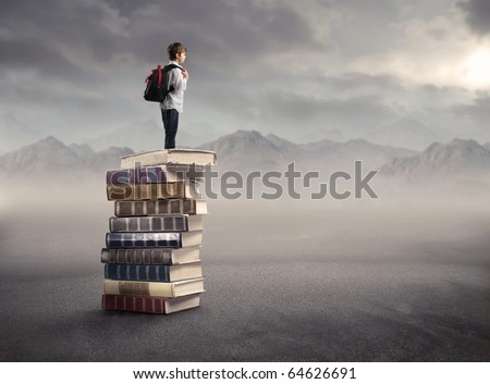 Child with rucksack standing on a stack of books - stock photo