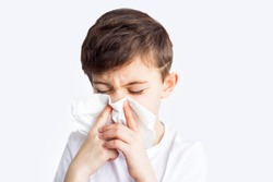Child with runny nose blows it into a paper handkerchief. illness flu in childhood. Worldwide epidemic of coronavirus covid-2019. Closed school. Health and medical care. Quarantine. Insurance.