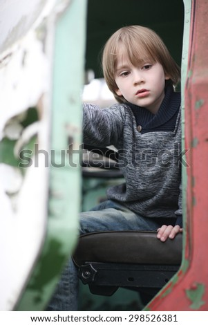 Child with sad facial expression getting out of an old driver cabin