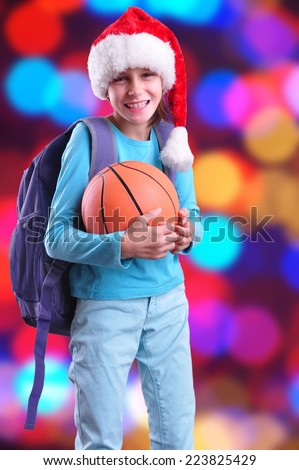 Child with Santa Claus red hat and ball. Christmas, New Year, holiday activities, sports celebration