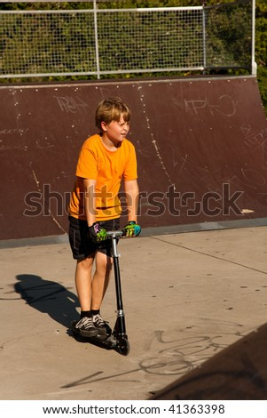 child with scooter and orange T-shirt is doing tricks at the scateboard parc and enjoying it