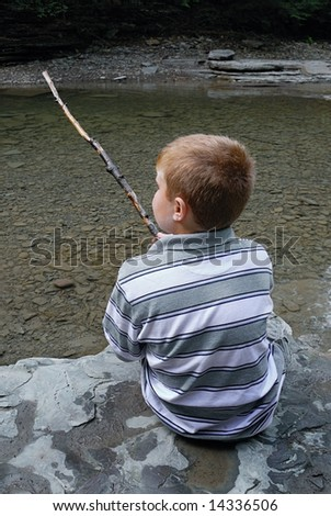 Child with stick enjoying a stream