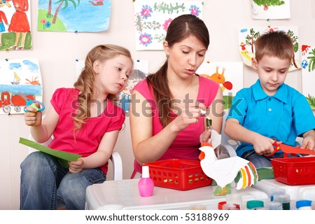 Child with teacher in play room. Preschooler.