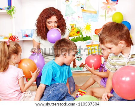 Child with teacher inflating balloons in school.