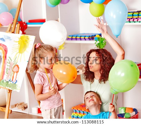 Child with teacher inflating balloons in school. - stock photo