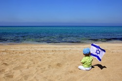 child with the flag of Israel on the beach