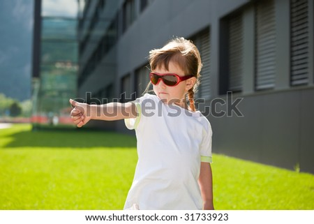 Child with trendy sunglasses showing thumb up on the background of modern building