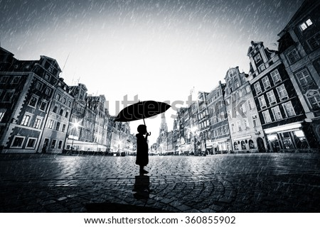 child with umbrella standing...