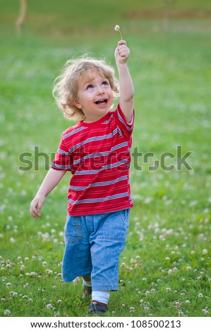 Child with white flower in the hand running over the green lawn