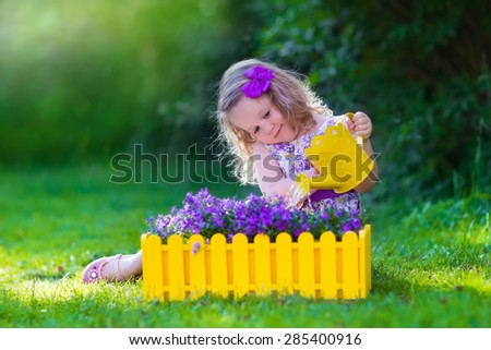 Child working in the garden. Kids gardening. Children watering flowers. Little girl with water can on a green lawn in the backyard in summer. Toddler kid playing outdoors planting purple flower pots.