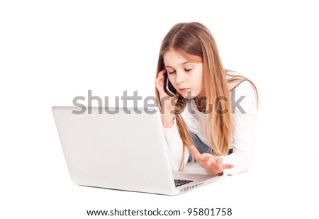 Child working on computer with phone at hands