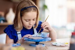 Child working on pottery wheel. Kids arts and crafts class in workshop. Little girl creating cup and bowl of clay. Creative activity in school.