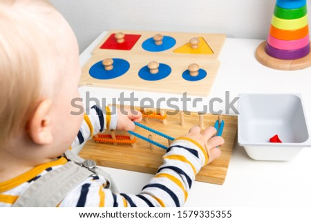 Child works with Montessori material for fine motor skills, sensory play. Playing children ストックフォト ©