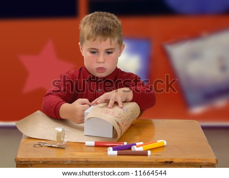 Child wrapping gift at school desk