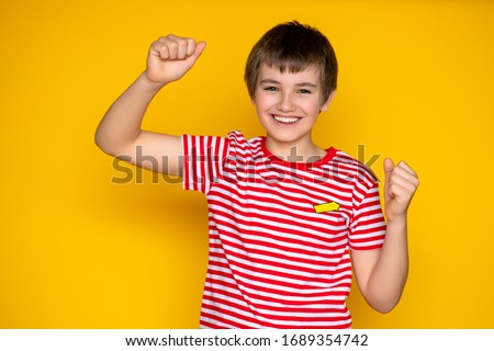 child 11-12 years old on a yellow background in a red T-shirt, various emotions of adolescence Stock photo ©