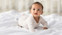Childcare Concept. Portrait of cute little African American baby wearing bodysuit lying on white beedsheets at home. Black infant child crawling on bed in the bedroom. Selective focus, free copy space