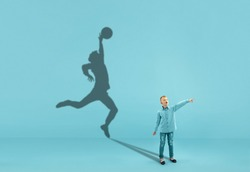 Childhood and dream about big and famous future. Conceptual image with boy and shadow of sportive male basketball player, champion on blue background. Childhood, dreams, imagination, education concept