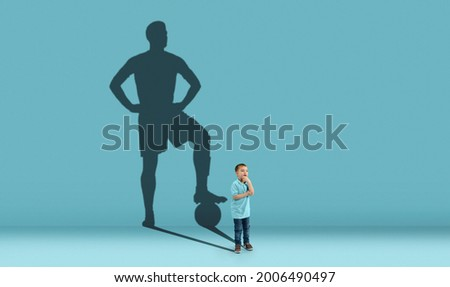 Childhood and dream about big and famous future. Conceptual image with boy and shadow of sportive male football player, champion on blue background. Childhood, dreams, imagination, education concept.