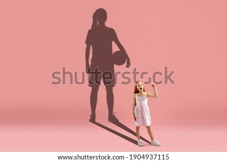 Childhood and dream about big and famous future. Conceptual image with girl and drawned shadow of basketball, soccer female player on coral pink background. Childhood, dreams, education concept.