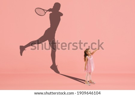 Childhood and dream about big and famous future. Conceptual image with girl and drawned shadow of female tennis player on coral pink background. Childhood, dreams, imagination, education concept.