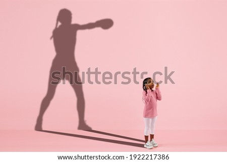 Childhood and dream about big and famous future. Conceptual image with girl and drawned shadow of female boxer on coral pink background. Childhood, dreams, imagination, education concept.