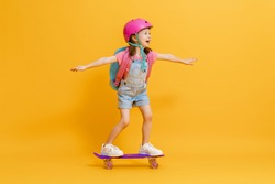 Childhood and happy time! Cute child with skateboard on color paper wall background. Kid with backpack. Girl ready to study.