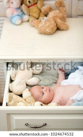 Childhood and innocence concept. Baby covered with white blanket lies near his soft toys. Newborn toddler with blue eyes and curious face. Infant lying in wooden chest drawer with teddy bears on top #1024674532