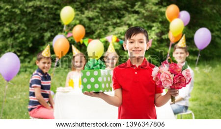 childhood and people concept - smiling little boy in polo t-shirt with gift box and flowers at birthday party over friends in summer park background #1396347806