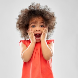 childhood and people concept - surprised or scared little african american girl screaming over grey background