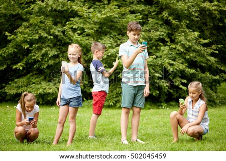 childhood, augmented reality, internet addiction, technology and people concept - group of kids or friends with smartphones playing game in summer park