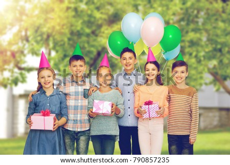childhood, birthday, friendship and people concept - happy smiling children in party hats with gifts and balloons over garden background #790857235