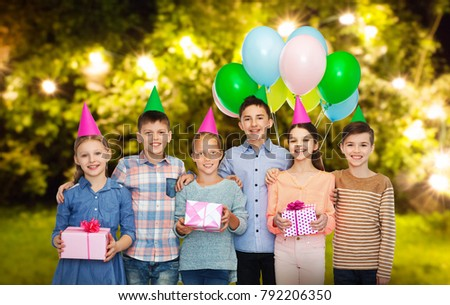 childhood, birthday, friendship and people concept - happy smiling children in party hats with gifts and balloons over festive lights at night garden background #792206350