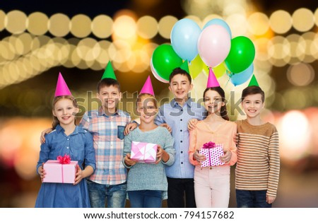 childhood, birthday, friendship and people concept - happy smiling children in party hats with gifts and balloons over festive lights background #794157682