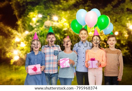 childhood, birthday, friendship and people concept - happy smiling children in party hats with gifts and balloons over festive lights at night garden background #795968374