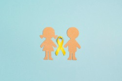 Childhood Cancer Awareness Yellow Ribbon with boy and girl cardboard dolls on blue background. Childhood Cancer Day February, 15.