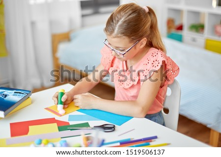 childhood, creativity and hobby concept - creative girl making greeting card and sticking pompon with glue stick at home #1519506137