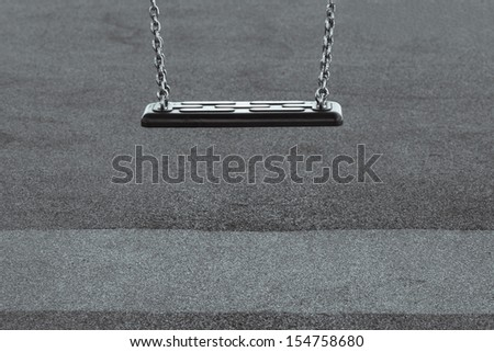 Childhood depression concept with single empty swing in black and white